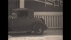 Vintage 16mm film, 1929, Chicago, man filling tires at gas station Stock Footage
