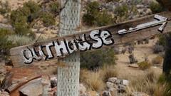 Close up of Outhouse Sign blowing in the wind - Mojave Desert - Riley's Camp Stock Footage