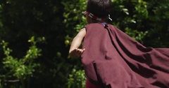 Two children play make believe heroes and villains in the park. slow motion. Arkistovideo