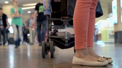 Two young moms with three babies shopping in the Mall with strollers and toys Stock Footage