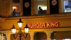 Hungary Budapest - night city street people eating in fast food burger king Stock Footage