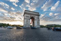 Arc de Triomphe and blurred traffic at sunset Stock Photos