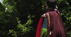 Children play pretend while dressed up as superheroes. Slow motion. Arkistovideo