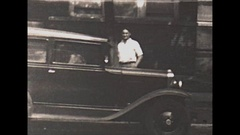 Vintage 16mm film, 1929, a man walks around his car and sits in it pretending... Stock Footage