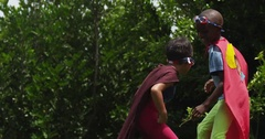 Two pint-sized superheroes play fight in their backyard. Slow motion. Arkistovideo