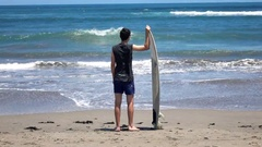 Young boy with surfing board standing near sea, super slow motion 240fps Stock Footage