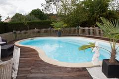 Beautiful house, swimming pool nobody inside, wooden deck Stock Photos