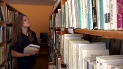Enthusiast smiling librarian woman working at library. Looking for books Stock Footage