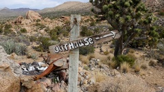 Outhouse Sign blowing in the wind - Mojave Desert - Riley's Camp Stock Footage