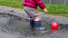 Child walking and jumping in a puddle Stock Footage