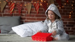 Cute little girl is unhappy with her Christmas gift by a fireplace in a her bed Stock Footage