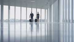 4K Business people traveling walking thru large open plan building with luggage Stock Footage