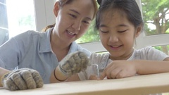 4K : Asian lovely girl helping her mother assembling new DIY furniture Stock Footage