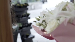 Pretty girl smelling flowers at flowershop, paris Stock Footage