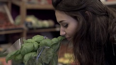 Pretty girl smelling basil plant at indoor market Stock Footage