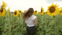 The girl happily running through a field of sunflowers, rejoicing and laughing. Stock Footage