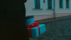Young Caucasian male carries a present white gift box with red ribbon bow Stock Footage