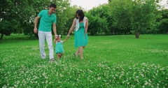 Young Asian family with year-old daughter walks in the Park holding hands, slow Stock Footage