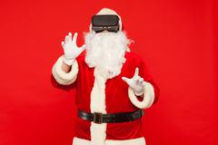 Santa Claus wearing virtual reality goggles, on a red background. Christmas Stock Photos