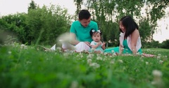 Young Asian family with a year-old baby in a Park during a picnic, have fun Stock Footage