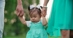Young Asian family with one year old baby walks in the Park holding hands, slow Stock Footage