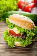 Cheeseburger with lettuce, onions and tomato in a sesame bun on wooden table Stock Photos