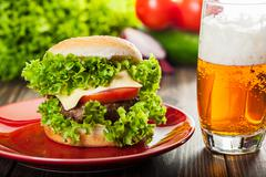 Cheeseburger on a plate with beer glass Stock Photos