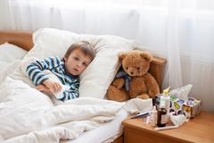 Sick child boy lying in bed with a fever, resting Stock Photos