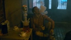 MED young Caucasian friends smoke a fragrant oriental hookah in a cafe Stock Footage