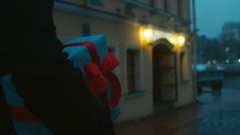 FOLLOW Young Caucasian male carries a present white gift box with red ribbon bow Stock Footage