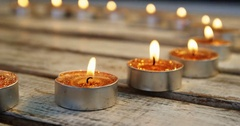 Close-up of burning candles kept in row on wooden plank Stock Footage