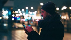 Adult men checking his mobile phone while standing on the street at night Stock Footage