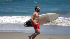Man with surfing board running on beach near sea, super slow motion 120fps Stock Footage