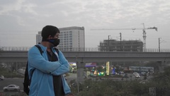 Man wearing a pollution mask in an urban landscape with construction and metro Stock Footage