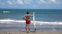 Man with surfing board standing on beach and admire view Stock Footage