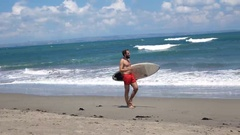 Young man with surfing board walking on beach near sea Stock Footage