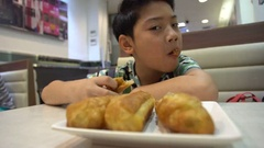 Happy asian preteens boy enjoy eating in morning breakfast. Stock Footage