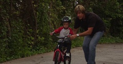Father steadies his son on a bike then lets go. Stock Footage