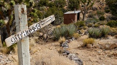 Outhouse Sign pointing to Outhouse - Mojave Desert - Riley's Camp Stock Footage