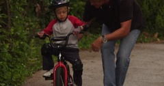 Father walks beside son, before sending the boy off to ride on his own power. Arkistovideo