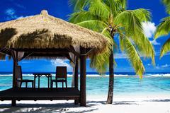 Tropical gazebo on amazing beach with palm tree Stock Photos