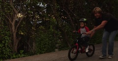 Sideview of father letting go and watching son ride bike. Stock Footage