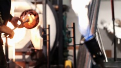 Glassblower heating a piece of glass in furnace Stock Footage