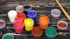 A lot of varicolored paint gouache jars with brushes on wooden background Stock Footage