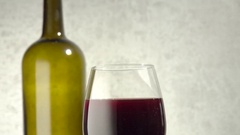 Red wine in glass with bottle in the background. Slow sliding motion. Stock Footage