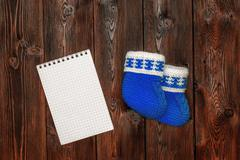 Blue hand made crochet baby booties and blank notebook, copyspace Stock Photos