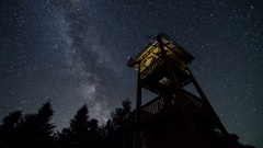 Stars sky with milky way turning over lookout tower time lapse. Starry night Stock Footage