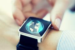 Close up of hand with globe hologram on smartwatch Stock Photos