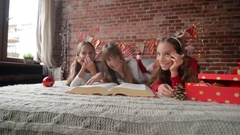 Three sisters lie on the bed in soft pajamas, Triplets read a huge book of Stock Footage