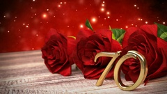 Seamless loop birthday background with red roses on wooden desk. seventieth Stock Footage